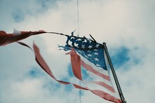 Low Angle View Of Abandoned American Flag Waving Against Cloudy Sky