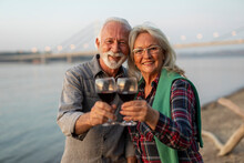 Portrait Of Happy Elderly Couple Drinking Wine On The Riverside And Toasting.