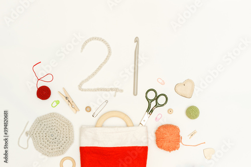 Items for knitting and needlework in a red stocking for gifts and numbers 21 mad Fototapet