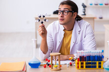 Young Male Chemist In Time Management Concept