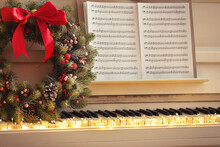 White Piano With Decorative Wreath And Note Sheets Closeup. Christmas Music