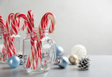 Candy Canes And Christmas Decor On Light Grey Table, Space For Text