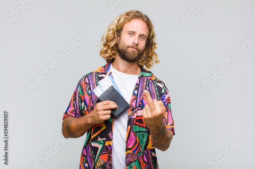 blonde man feeling angry, annoyed, rebellious and aggressive, flipping the middle finger, fighting back