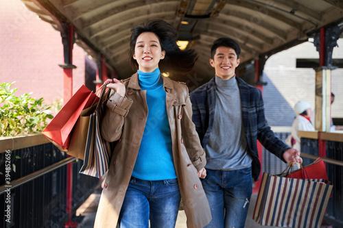 young asian couple running on footbridge with shopping bags Tapéta, Fotótapéta