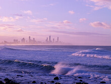 Looking Across Rolling Waves And Ocean At Surfers Paradise Skyline Of City
