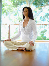 Woman Sitting Crossed Legged In Meditation Position On Wooden Floor Against Outdoor Background