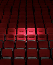 Spot Light Shining On A Few Red Seats In Rows Of Seats In Auditorium