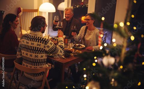 Obraz Family enjoying Christmas dinner with drinks - fototapety do salonu