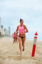Female Surf Lifeguards Training On The Beach Running Towards Marker In The Sand