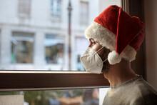 Ragazzo Con Cappello Da Babbo Natale E Mascherina Ffp2 Guarda Triste Fuori Casa Attraverso Il Vetro Di Una Finestra