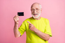 Photo Of Old Happy Cheerful Smiling Grandfather Wear Lime T-shirt Point Finger At Credit Card Isolated On Pink Color Background