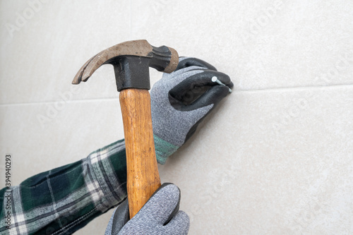 Fotomural Man's hand holding a hammer and nailing the wall.