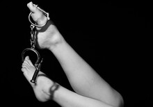 Low Section Of Woman With Handcuffs Against Black Background