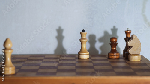 Foto Wooden chess pieces and a chessboard with drop shadows on the wall, selective fo