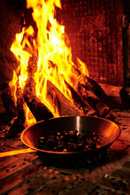 Chestnuts Roasting Over The Fire In A Typical Frying Pan Over A Fireplace. Rural Concept And Village Tradition