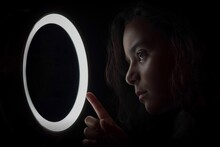 Close-up Of Girl Looking At Illuminated Circle Against Black Background