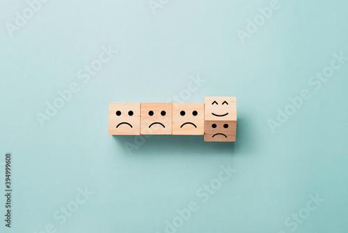 Obraz na plátně Flipping of wooden cube block from sad to smile emotion on blue background