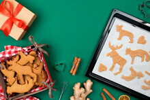 Top View Of Christmas Gingerbread Cookies From Raw Dough On  Baking Tray, Ginger, Cinnamon, Deer Shaping Biscuit, Freshly Backed Cookies On Red Plaid Napkin, Gift Over Green. Winter Holidays Flat Lay