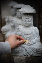 Cropped Hand Of Woman Putting Money On Buddha Statue