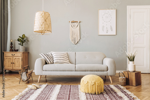 Stylish and design home interior of living room with gray sofa, wooden cubr , pillows, blankets, rattan lamp,  flowers, basket and elegant accessories. Stylish home decor. Template.