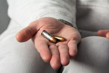 A Man's Hand Open With A Nine Millimeter And A Forty-five Millimeter Bullets