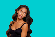 Beauty Styled Portrait Of A Young African American Woman. Makeup. Fashion Black Girl With Curly Hair Posing In The Studio On A Turquoise Background. Isolated. Studio Shot.