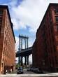 Cars Parked On Street Amidst Buildings Against Manhattan Bridge