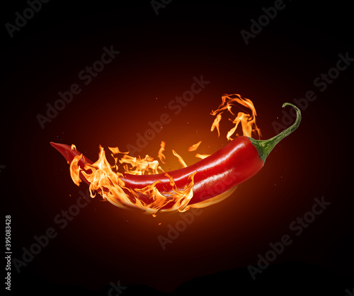 Canvastavla Red chili pepper close-up in a burning flame on a black background