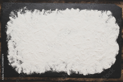 Fotografie, Tablou Sifted wheat flour over dark grey texture surface