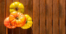 View From Above On Four Green And Ripe Red Village Tomatoes Lying On Brown Wooden Surface. Natural Food Background With Copy Space. Sun Light Reflecting On Fruits.