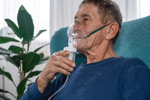 Foto elderly senior sits in a armchair with an oxygen mask in quarantine at home