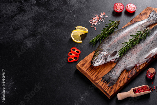 Foto Raw trout lie on a black stone chopping board on a dark concrete table