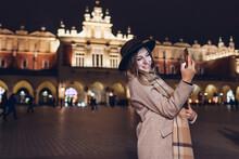 Tourist Woman Taking Selfie On Smartphone At Night On Market Square In Krakow Poland. Travel Around Europe