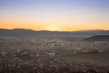 Beautiful, Misy Pirot Cityscape During Golden Hour, Setting Sun And Distant Horizon Mountains