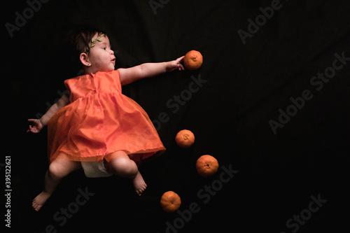 Slika na platnu Niña pequeña en vestido naranja tratando de alcanzar una mandarina