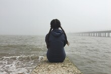Rear View Of Teenage Girl Sitting On Pier Over Sea Against Clear Sky
