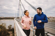 canvas print picture Smiling happy sporty couple jogging on the bridge at cloudy autumn day.