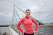 canvas print picture Smiling beautiful fit sportswoman standing on the bridge at cloudy autumn day with hands on hips and looking at camera.