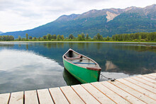 A Canoe Tied To A Dock With Mountains In The Background