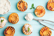 Delicious grilled peaches, ice cream and mint on light blue wooden table, flat lay