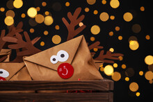 Gifts In Envelopes With Deer Faces In Wooden Crate Against Blurred Lights, Closeup. Christmas Advent Calendar