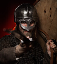Portrait Of Viking Wearing Helmet While Holding Sword And Shield