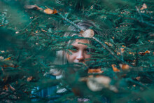 The Girl's Gaze Through The Foliage In The Woods.
