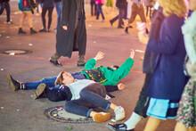 Drunk Men Lying On Road At Amusement Park During Night