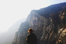 Rear View Of Man Standing Against Mountains During Foggy Weather