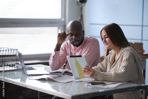 Fotografiet young African-American man with female colleague while working in cubicle at office
