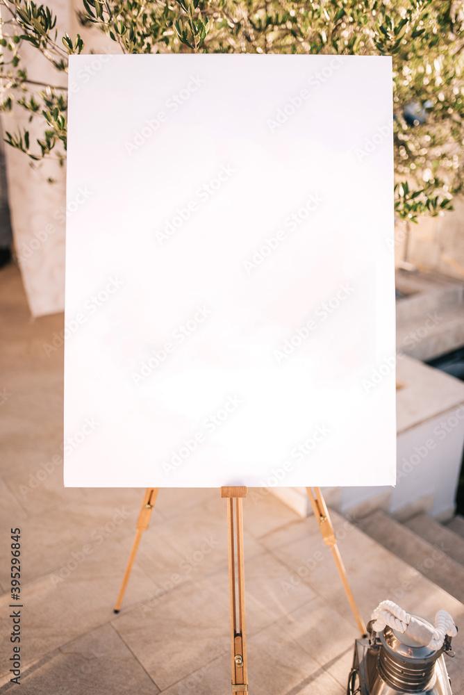 Fototapeta Wooden easel with white paper