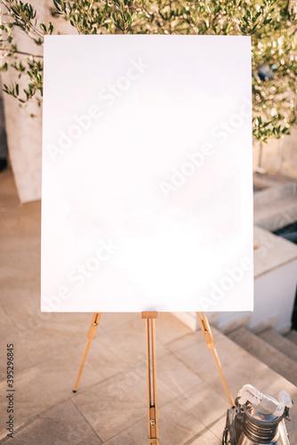 Wooden easel with white paper Fototapeta