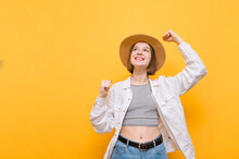 Portrait Of Happy Woman In Hat And Summer Clothes Rejoices With Raised Hands On Yellow Background, Looks Up At Copy Space. Joyful Lady Tourist Isolated On Orange Background.
