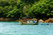 Fishing Trawler Anchored Along The Rocks And Forest By The Sea In Trindade, Rio De Janeiro, Brazil